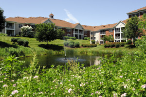 Exterior View of Independent Living Apartments with Lawn and Water Feature in Foreground