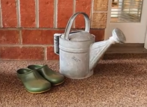 Watering can and gardening shoes on the porch